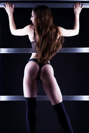 Beautiful sexy woman posing in black underwear on light wall in dark studio