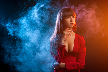 Young dark-haired woman in a red dress posing against a background of red and red smoke from a vape on a black isolated background