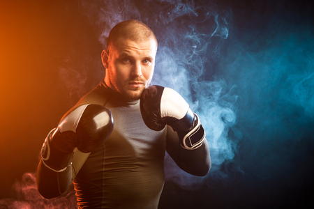 A strong young dark-haired male athlete in a green sports jacket, in black and white boxing gloves boxing against a background of blue and red smoke on a black isolated background Stock fotó