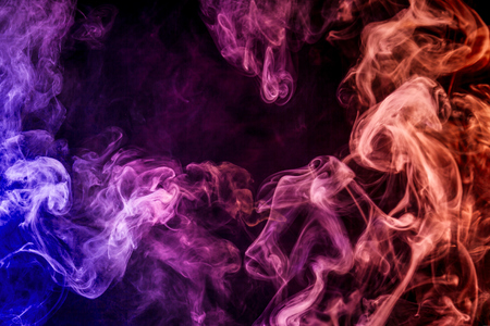 Thick colorful smoke of red, blue, purple on a black isolated background. Background from the smoke of vape