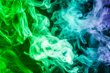 Colorful smoke of blue, green on a black isolated background. Background from the smoke of vape