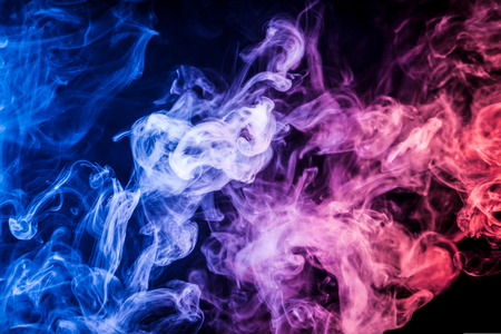 Dense multicolored smoke of   blue, red  and pink colors on a black isolated background. Background of smoke vape