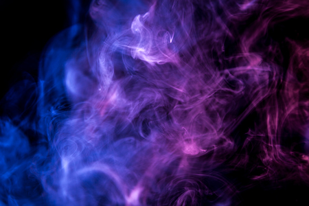 Colorful smoke of blue, pink, purple on a black isolated background. Background from the smoke of vape