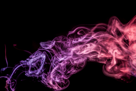 Dense multicolored smoke of  pink colors on a black isolated background. Background of smoke vape