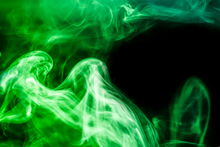 Colorful smoke of red on a  green isolated background. Background from the smoke of vape