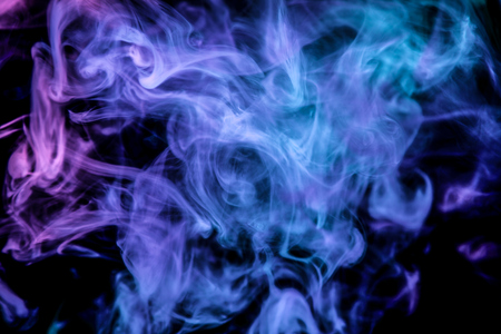 Dense multicolored smoke of blue and pink colors on a black isolated background. Background of smoke vape Standard-Bild
