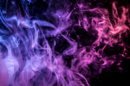 Thick colorful smoke of   blue and purple on a black isolated background. Background from the smoke of vape