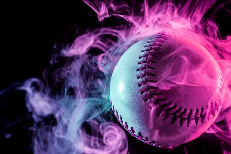 黒い孤立した背景の蒸気から多色の赤い煙で白い野球ボール