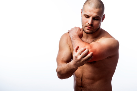 Injury of the elbow. Young bald man sports physique holds a sick elbow on a white isolated background Stock Photo