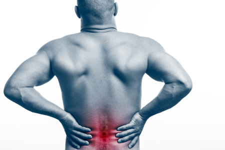 Injury of the spine. Young bald man sports physique holds a sick back on a white isolated background. Fracture of spine