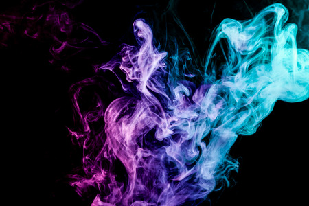 Thick colorful smoke of pink and blue on a black isolated background. Background from the smoke of vape Stok Fotoğraf