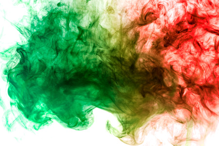 Dense multicolored smoke of red, green and yellow colors on a white isolated background. Background of smoke vape