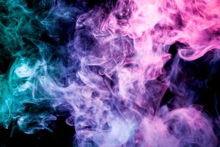 Dense multicolored smoke of blue, pink and purple colors on a black isolated background. Background of smoke vape