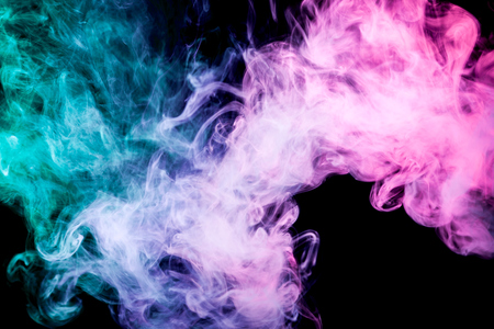 Thick colorful smoke of pink, blue, green on a black isolated background. Background from the smoke of vape Stock Photo