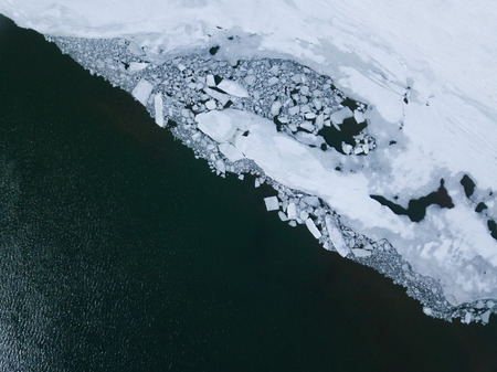 A blue river, covered with smoothness and cracked ice, is a top view. Ice drift with quadrocopter