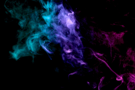 Thick colorful smoke of  purple, blue and  green on a black isolated background. Background from the smoke of vapee