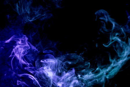 Dense multicolored smoke of blue and purple colors on a black isolated background. Background of smoke vape