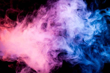 Dense  blue and pink multicolored smoke on a black isolated background. Background of smoke vape