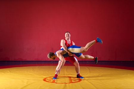 Two strong wrestlers in blue and red wrestling tights are wrestlng and making a  making a hip throw  on a yellow wrestling carpet in the gym. Young man doing grapple. Stock Photo