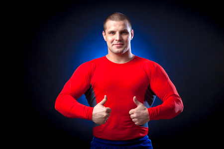 A strong dark-haired sportsman in a red sports wear rush guard shows thumb up and posing against a blue a lights on a black isolated background