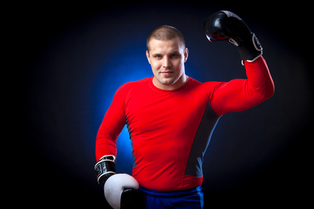 A strong dark-haired sportsman boxer in a red sports wear rush guard and in black and white boxing gloves smile and standing against a blue a lights on a black isolated background