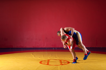 Two greco-roman  wrestlers in red and blue uniform wrestling  on a yellow wrestling carpet in the gym. Young man grappling