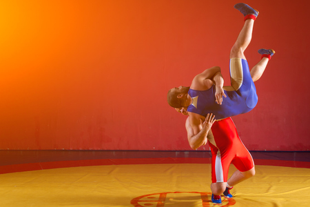 Two greco-roman  wrestlers in red and blue uniform making a   hip throw  on a yellow wrestling carpet in the gym