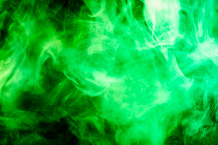 Colorful  green smoke  on a black isolated background. Background from the smoke of vape