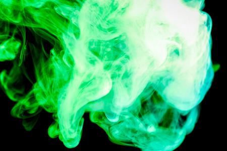 Dense green multicolored smoke on a black isolated background. Background of smoke vape