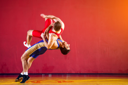 Two strong wrestlers in blue and red wrestling tights are wrestlng and making a  making a hip throw  on a yellow wrestling carpet in the gym. Young man doing grapple. Фото со стока