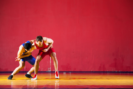 Two strong wrestlers in blue wrestling tights are wrestlng and making a suplex wrestling on a yellow wrestling carpet in the gym. Young man doing grapple.