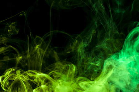 Thick colorful smoke of green and blue on a black isolated background. Background from the smoke of vape Imagens