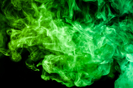 green cloud of smoke of  black isolated background. Background from the smoke of vape