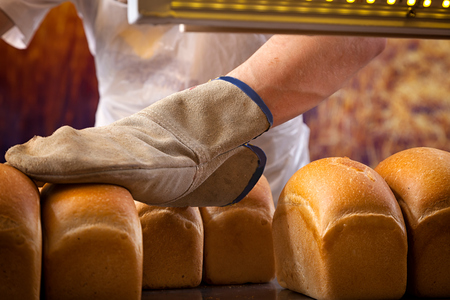 A close-up of a bakers man in a protective glove touches a freshly baked fresh bread, which he just took out of the oven