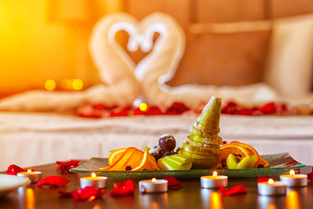 Romantic dinner for lovers: a table with a fruit plate and candles, in the background a bed decorated with swans of towels and rose petals