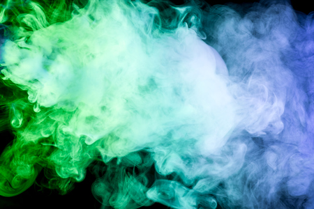 Colorful green, blue and yellow smoke  on a black isolated background. Background from the smoke of vape