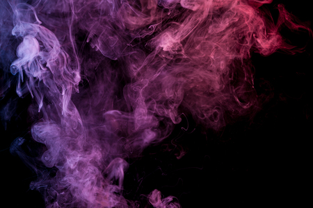 Pink and purple cloud of smoke of  black isolated background. Background from the smoke of vape