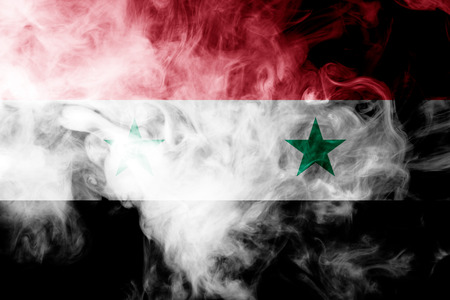 National flag of Syria from thick colored smoke on a black isolated background