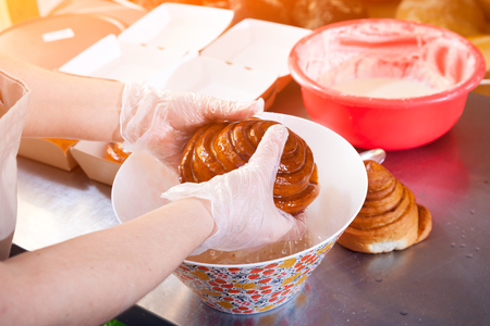 A close-up of a female baker in protective gloves  prepares buns cinnabon and pours cream on them in bakery