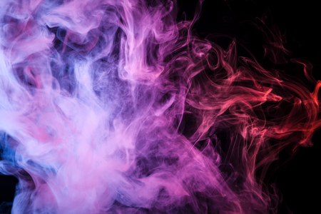 Blue, red  and pink  cloud of smoke of  black isolated background. Background from the smoke of vape