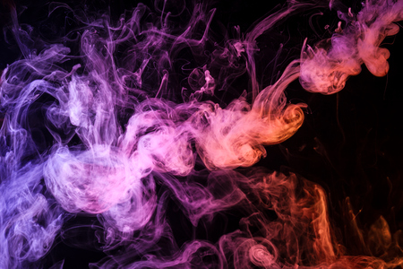Thick colorful smoke of pink, blue and red on a black isolated background. Background from the smoke of vape