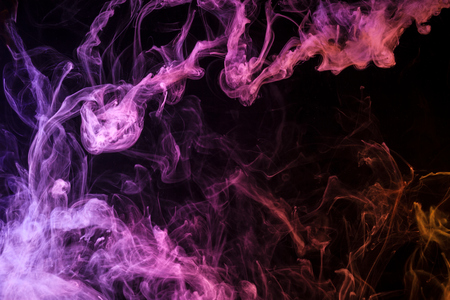 Thick colorful smoke of pink, purple and red on a black isolated background. Background from the smoke of vape