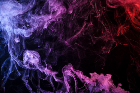 Yellow  and pink  cloud of smoke of  black isolated background. Background from the smoke of vape