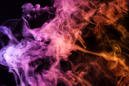 Colorful pink and orange smoke  on a black isolated background. Background from the smoke of vape  Stock Photo