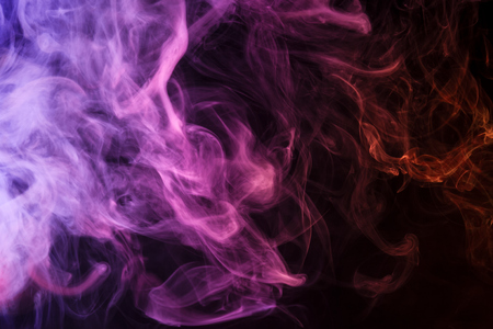 Colorful red, pink and orange smoke  on a black isolated background. Background from the smoke of vape
