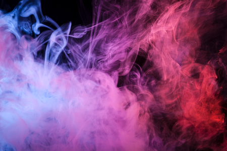 Colorful pink,red and blue smoke  on a black isolated background. Background from the smoke of vape