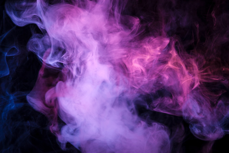 Thick colorful smoke of pink, purple blue on a black isolated background. Background from the smoke of vape