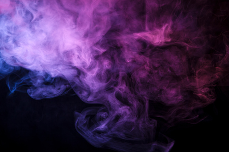Colorful pink, blue and red smoke  on a black isolated background. Background from the smoke of vape  Stock Photo