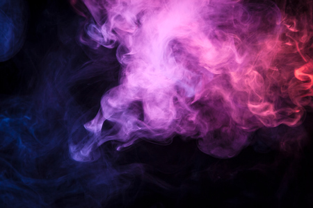 Colorful pink and red smoke  on a black isolated background. Background from the smoke of vape  Stock Photo