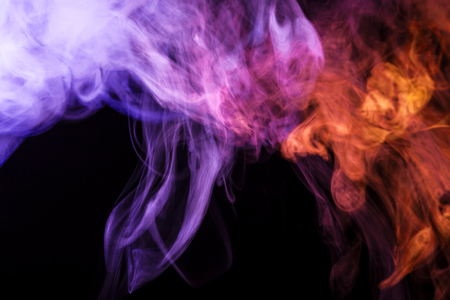 Colorful blue, pink and red smoke  on a black isolated background. Background from the smoke of vape  Stock Photo
